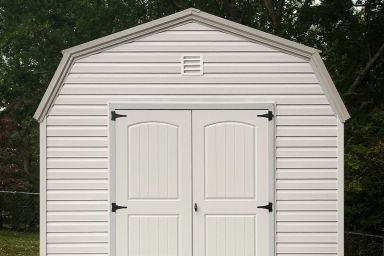 A portable building in Kentucky with vinyl siding and double doors on a concrete foundation