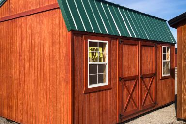 A portable building in Kentucky with wood siding and a green metal roof