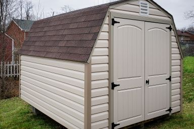 A portable building in Kentucky with vinyl siding and a shingle roof