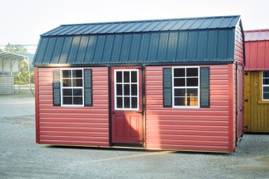 A lofted shed in Kentucky with red vinyl siding and a black metal roof