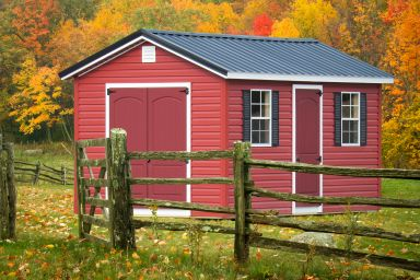A shed in Kentucky with red vinyl siding and a metal roof on a fall day