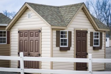 A shed in Kentucky with vinyl siding and a shingle roof with a dormer