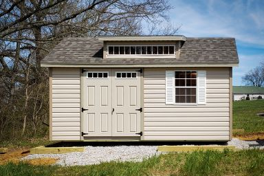 A vinyl shed in Kentucky with double doors, windows, and a roof dormer