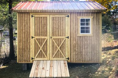 A wooden shed in Kentucky with double doors and a ramp