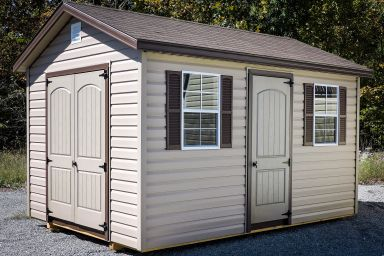A brown vinyl shed in Tennessee with double doors, windows, and shutters