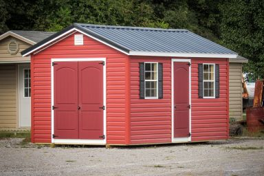 A shed in Tennessee with red vinyl siding and a metal roof