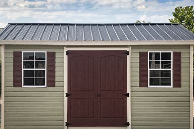 A shed in Tennessee with green vinyl siding and a metal roof