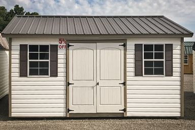 A discounted shed in Tennessee with white vinyl siding and a metal roof