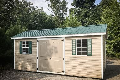 A shed in Tennessee with vinyl siding and a green metal roof