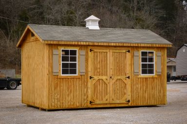 A shed in Tennessee with wooden siding and a shingle roof with a cupola
