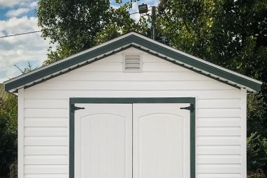 A garden shed in Kentucky with vinyl siding and a green metal roof