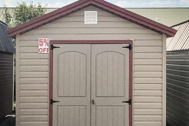 A discounted garden shed in Kentucky with vinyl siding, double doors, and a red metal roof