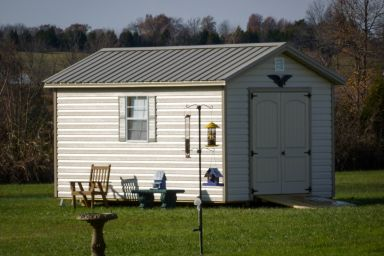 A storage shed in Kentucky with vinyl siding, double doors, and a metal roof