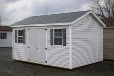 A storage shed in Kentucky with white vinyl siding, double doors, and a shingle roof