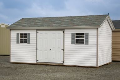 A storage shed in Kentucky with vinyl siding, double doors, and windows with shutters