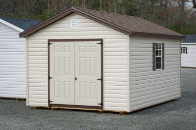 A storage shed in Kentucky with vinyl siding, double doors, and a brown shingle roof