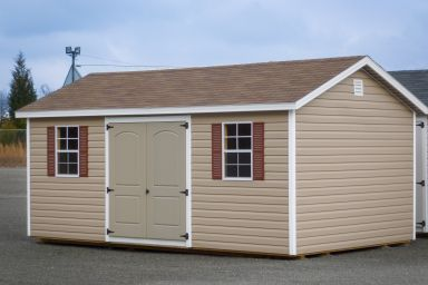 A storage shed in Kentucky with brown vinyl siding, double doors, and windows with shutters