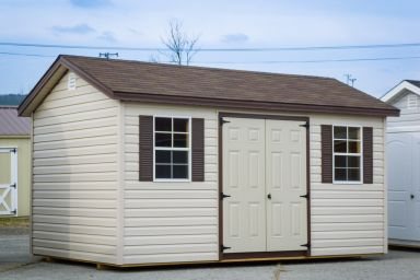 A storage shed in Kentucky with vinyl siding, double doors, and windows with brown shutters