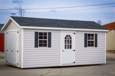 A storage shed in Kentucky with vinyl siding, double doors, and a black shingle roof
