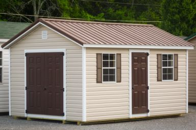 A storage shed in Kentucky with vinyl siding, double doors, and a brown metal roof