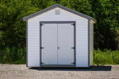 A storage shed in Tennessee with white vinyl siding and double doors