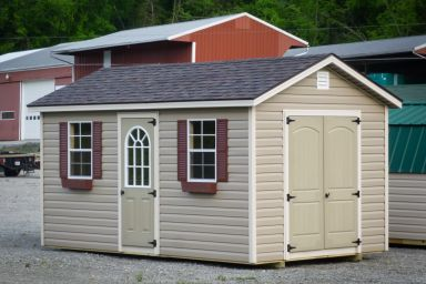 A storage shed in Tennessee with vinyl siding, double doors, and windows with flower boxes