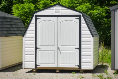 A backyard shed in Kentucky with white vinyl siding and double doors