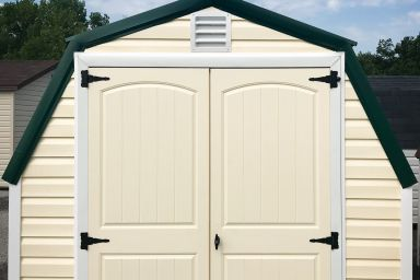 A backyard shed in Kentucky with yellow vinyl siding and double doors