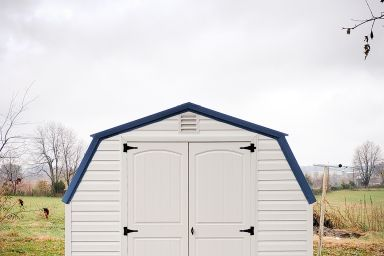 A backyard shed in Kentucky with white vinyl siding, a blue metal roof, and double doors