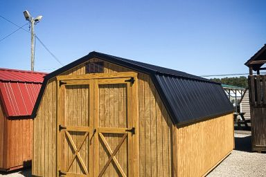 A portable shed in Tennessee with wooden siding, a black metal roof, and double doors