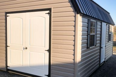 An outdoor shed in Kentucky with vinyl siding, two windows, and a black metal roof