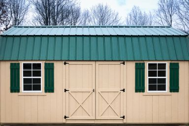 An outdoor shed in Kentucky with painted wood siding, two windows, and a green metal roof