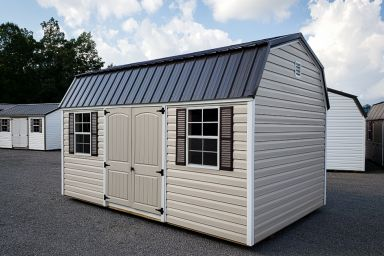 A barn-style outdoor shed in Tennessee with vinyl siding, double doors, and a metal roof