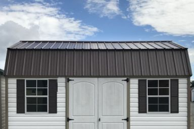 An outdoor shed in Tennessee with vinyl siding, double doors, and two windows
