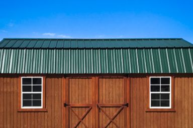 An outdoor shed in Tennessee with wood siding, double doors, and two windows