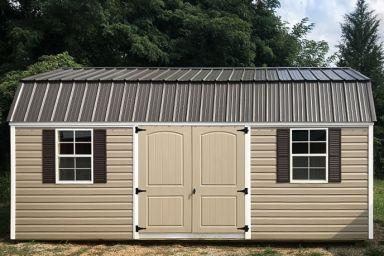 A lofted outdoor shed in Tennessee with vinyl siding, double doors, and a metal roof