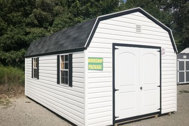 An outdoor shed workshop in Tennessee with vinyl siding, double doors, and a shingle roof