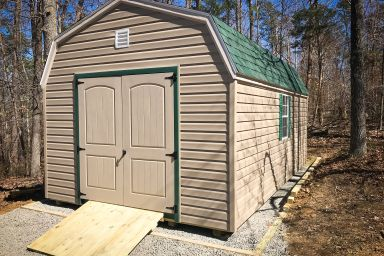 An outdoor shed in Tennessee with vinyl siding, double doors, and a green shingle roof