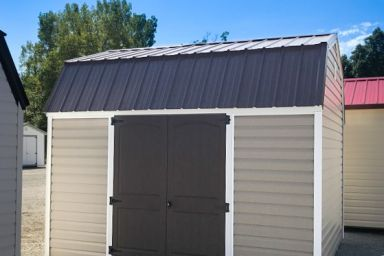 An outdoor shed in Tennessee with vinyl siding and a black metal roof