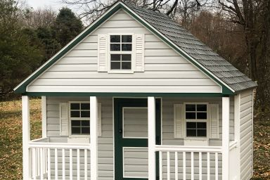 A prefab cabin playhouse in Kentucky with vinyl siding and a front porch