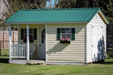 A prefab cabin in Tennessee with vinyl siding and a green metal roof
