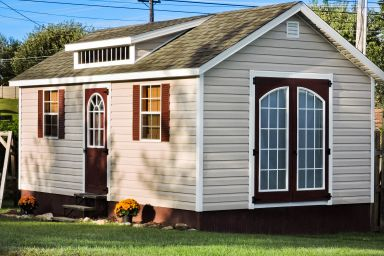A prefab cabin in Tennessee with vinyl siding, double doors, and a roof dormer