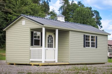 A prefab cabin in Tennessee with vinyl siding, a corner porch, and a cupola