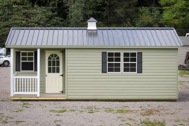 A prefab cabin in Tennessee with vinyl siding and metal roof with a cupola