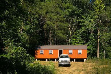 A small cabin for sale in Kentucky with wooden siding and a metal roof