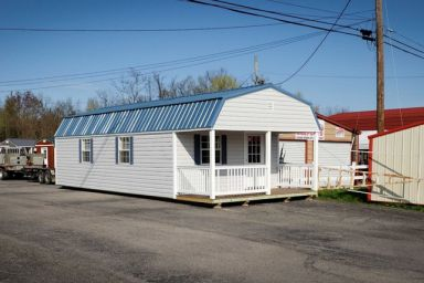 A small cabin for sale in Kentucky with vinyl siding and a front porch