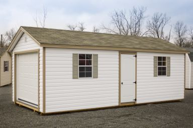 A portable garage in Kentucky with vinyl siding and a shingle roof