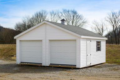 A multiple-car prebuilt garage in Kentucky with white vinyl siding and a cupola