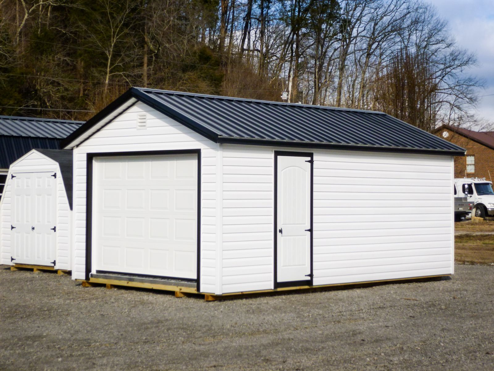 A garage shed in Kentucky with vinyl siding and a black metal roof