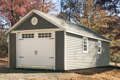 A single-car garage shed in Tennessee with green vinyl siding and windows